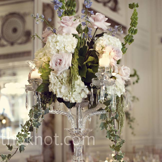 One of three different centerpiece designs, arrangements of roses, hydrangeas, bells of Ireland, belladonna delphiniums, and ivy atop tall crystal candelabras embodied the same timeless, romantic vibe as the rest of the decor.