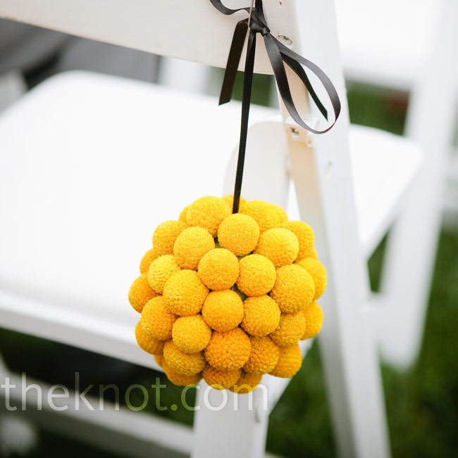 Craspedia pomanders added a pop of color to the white garden chairs.