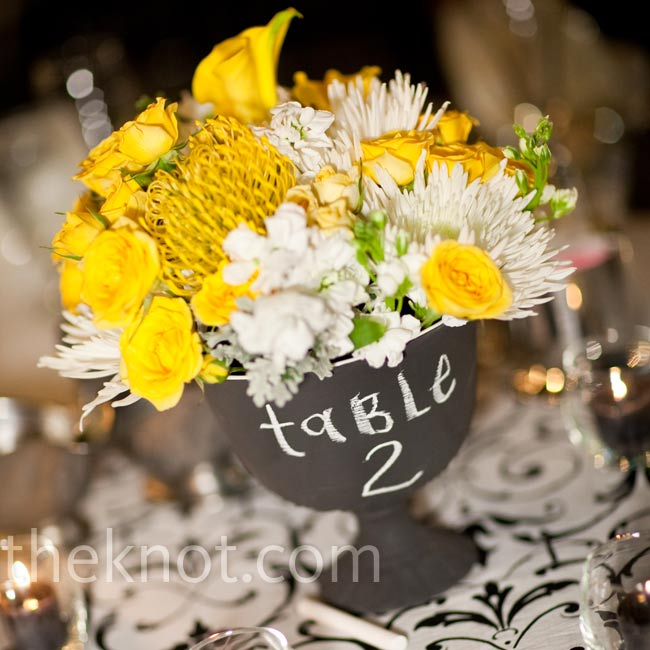 The couple decided on low yellow-and-white centerpieces after falling in love with these chalkboard vases that conveniently doubled as table numbers.