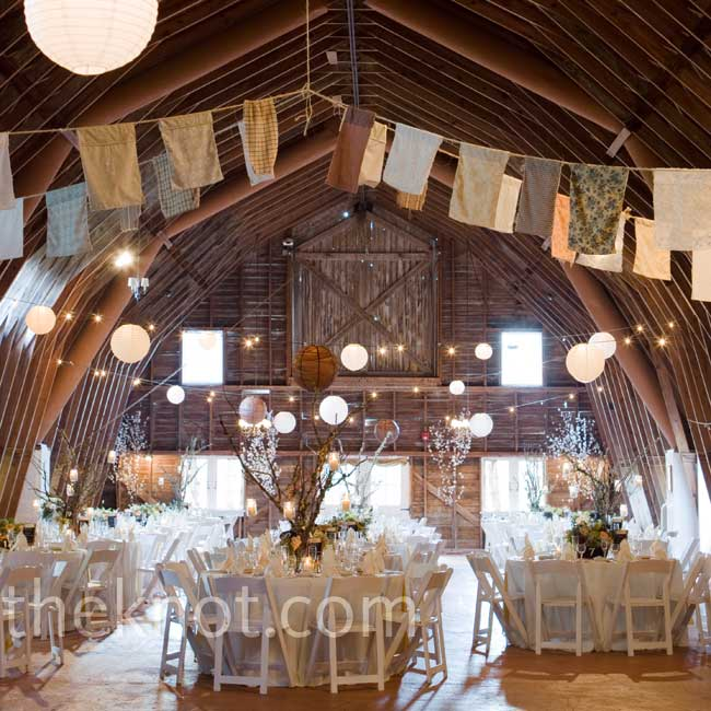 Cream linens and white chairs provided a neutral base, letting the rustic interiors shine. Varied strips of fabric hung from the rafters for a homespun feel.