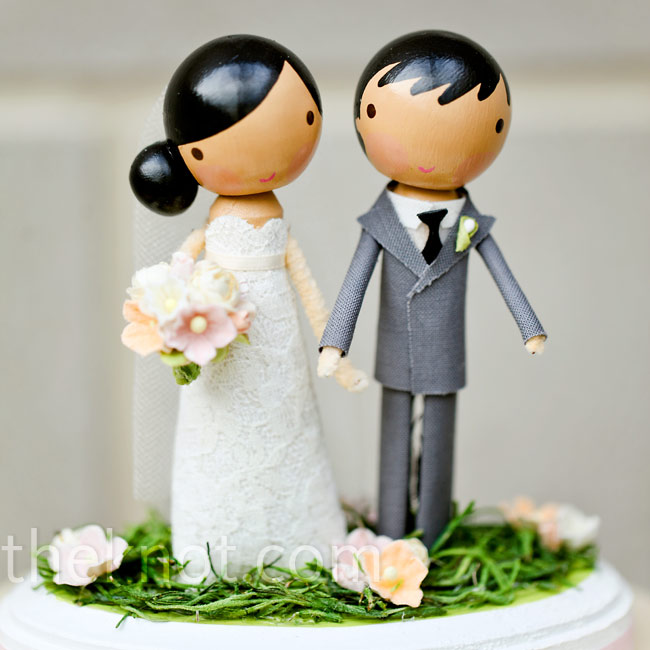 Custom wooden toppers in the couple's likenesses put a signature stamp on the largest of their there cakes.