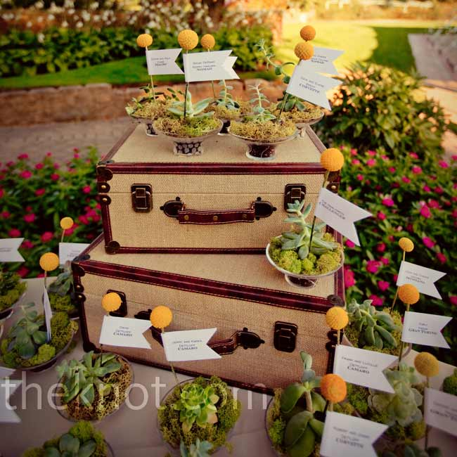 Although seating wasn't assigned at dinner, favors of potted succulents with personalized flags were arranged around vintage suitcases for guests to take as they entered the reception to mark their chosen seats.