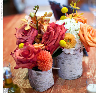 A cluster of birch bark vases (made by the couple's florist) held a vibrant mix of roses, dahlias and orchids.