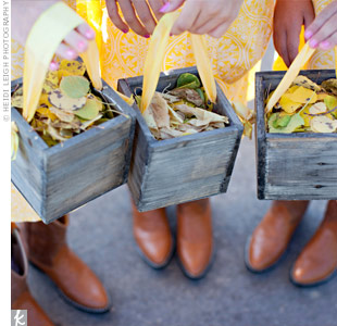 Wearing matching cowboy boots and yellow dresses, Rachelle's three cousins scattered golden aspen leaves along the aisle.