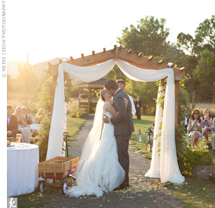 The couple got engaged in a tent, so they exchanged vows under a wooden archway that was decorated like a tent, complete with white fabric and zip ties.