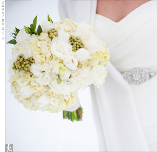 Stacy carried an all-white bouquet of hydrangeas, tulips, and ranunculus mixed with juniper berries.