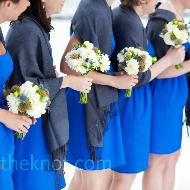 Yellow freesias and blue thistle added vibrant pops of color to the bridesmaids' white dahlia bouquets.
