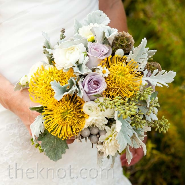 Neutral-colored elements, like dusty miller leaves and silver brunia berries, let the yellow pincushion proteas in Alexis's bouquet stand out.