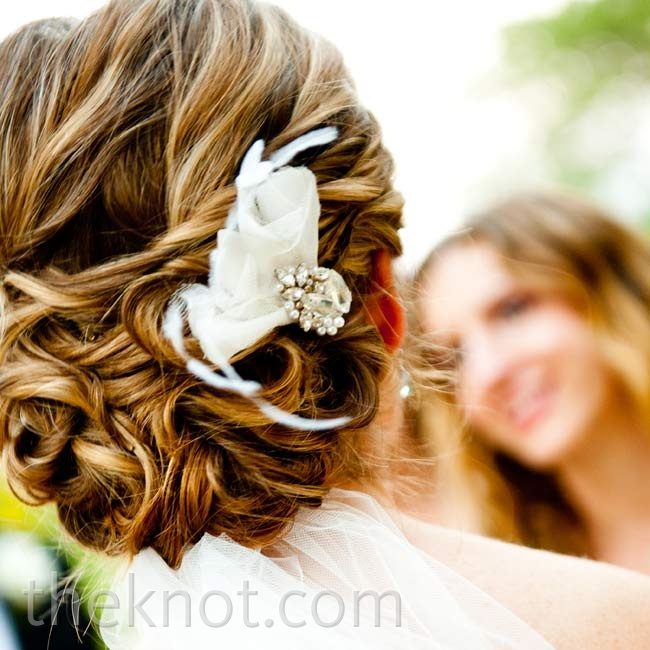 Alexis tucked a simple ostrich feather hairpiece into her curly updo.