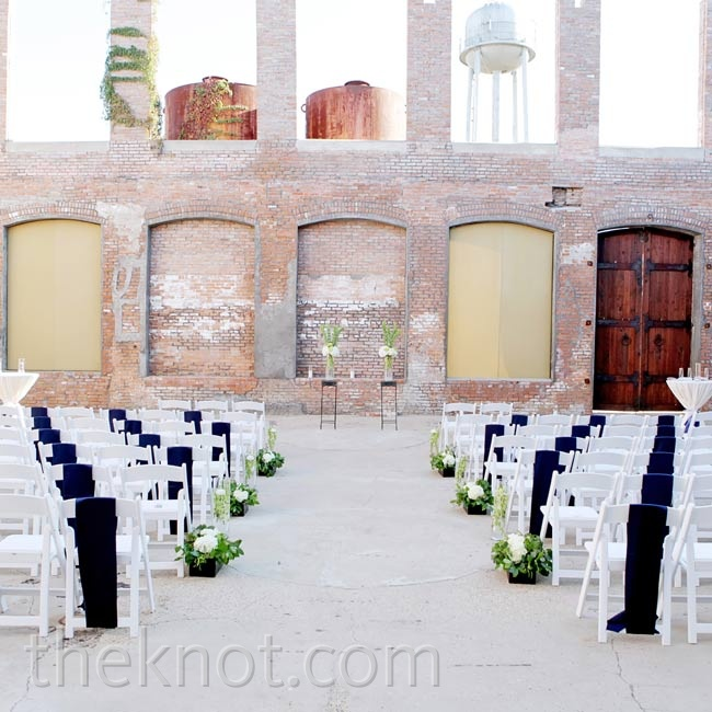 With exposed brick and open-air windows, the space didn't need much else: just some simple aisle and altar arrangements and navy sashes on every other chair.