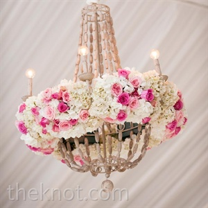 Chandeliers rimmed with florals added color and life to the plain tent setting.