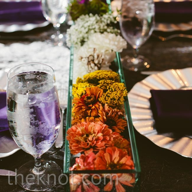 A long glass tray holding a rainbow of blooms was an eye-catching focal point for the head table.