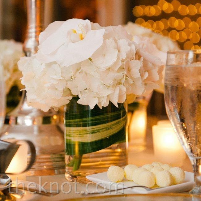 Small arrangements of hydrangeas and orchids dressed up the bases of the tall, thin centerpieces.