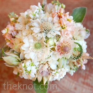 Sarah carried a romantic bouquet of soft blooms like blushing bride proteas, scabiosa, and stock.