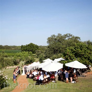 White market umbrellas shaded guests during the outdoor ceremony.