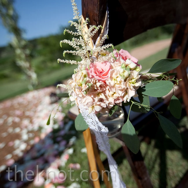 Mini pink bouquets wrapped in lace ribbon marked the ceremony aisle.