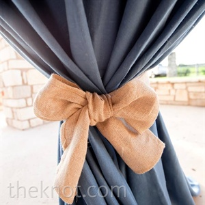 The cocktail tables at the reception were draped in blue linens tied with burlap bows.