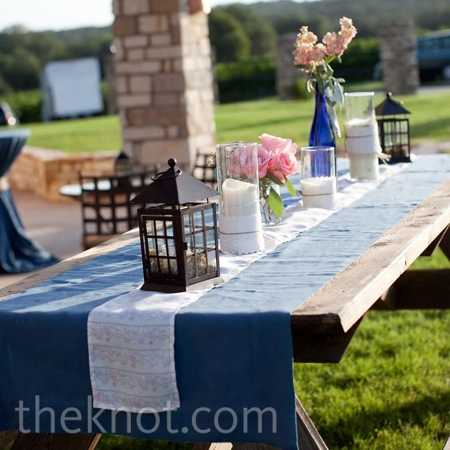 Simple table runners, lanterns, and floral arrangements on picnic tables kept the reception looking totally relaxed.