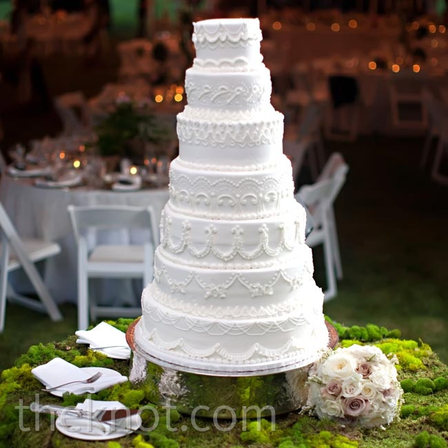 The white cake, with different designs on each of its seven tiers, was displayed on a moss cloth made by Ashley's mom.
