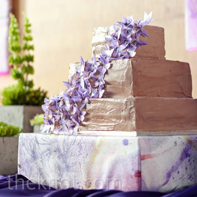 The three-tiered square cake was covered in a Nutella buttercream frosting and cascading edible flowers.
