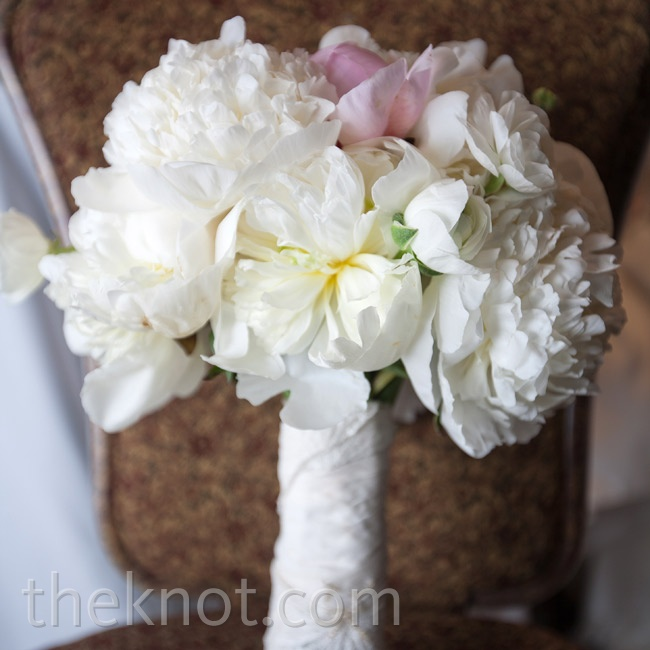 Kendra's bouquet (of white, ivory, and blush blooms) was wrapped in fabric from her great-grandmother's wedding dress.