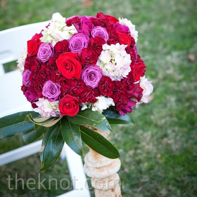 Vibrant bunches of pink, fuchsia and white hues popped against the ceremony aisles.
