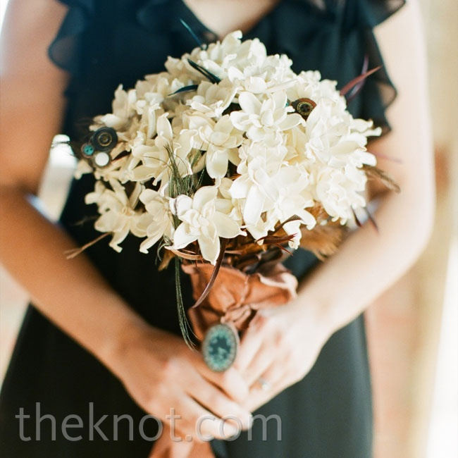 Vintage buttons and feathers were a playful addition to the bridesmaid's all-white arrangement of balsa wood gardenias.