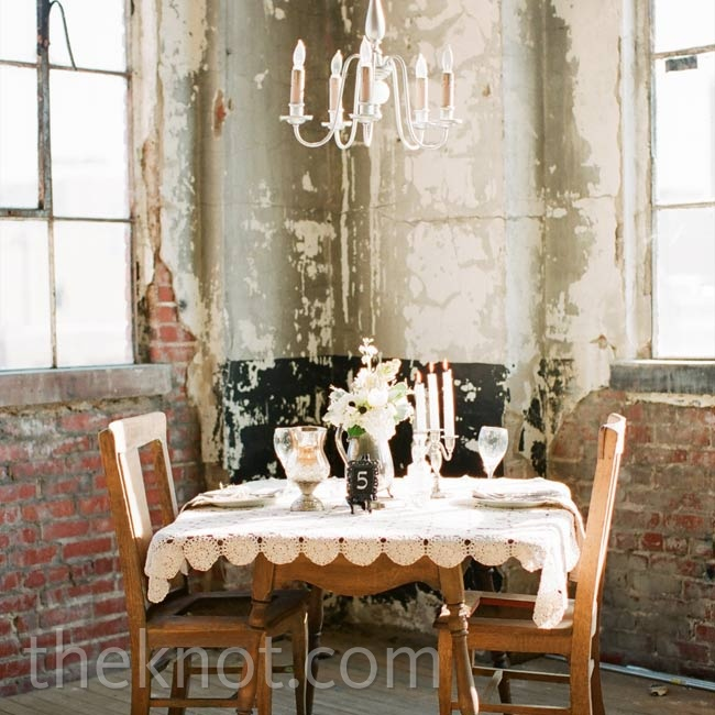 A mix of vintage items, like bronze photo frame table numbers, mercury glass votives and candelabras, topped tables.