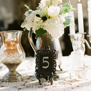 Framed table numbers sat next to centerpieces in vintage pitchers.