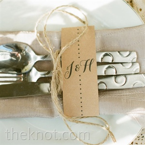 Silverware was tied with twine, placed atop tan napkins and labeled with the couples initials.