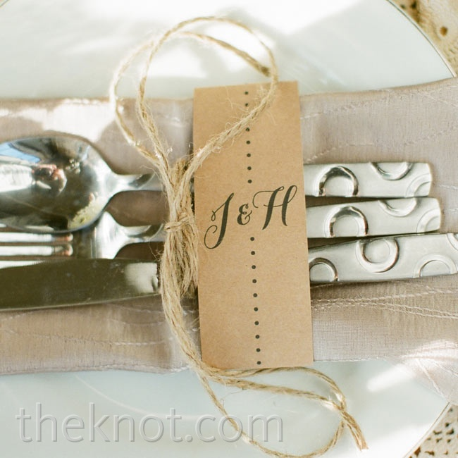 Silverware was tied with twine, placed atop tan napkins and labeled with the couple's initials.