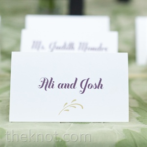 Tented escort cards printed with a deep-purple type guided guests to their seats.
