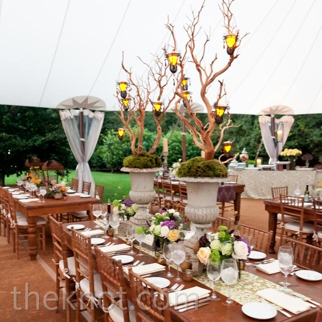 Long, farm-style wooden tables and stone urns created a homey vibe inside the sailcloth reception tent.