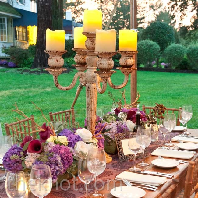 Wanting to create a warm setting, Alison and Josh decorated the tables with an eclectic mix of items; giant aged candelabras, fabric runners, and low, lush arrangements.