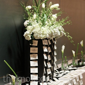 Oversize arrangements  of calla lilies, hydrangeas, and dendrobium orchids drew attention to the escort card table.