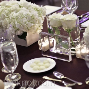 Aubergine satin linens and Lucite elements topped the reception tables.