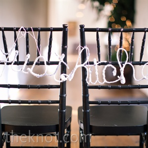 "A ""just hitched"" sign hung on the bride's and groom's chairs. Katie made it herself, out of wire and yarn."