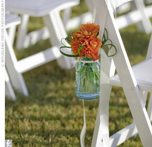 Antique turquoise jars filled with orange dahlias hung from the chairs lining the grassy aisle.