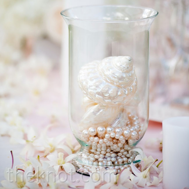 To accent the centerpieces running down the long dining tables, Zeina put together non-floral arrangements of seashells and strands of pearls set in hurricane vases.