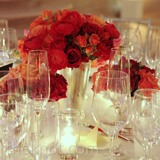 Roses and ranunculus in mint julep cups, arranged with votive candles, gave the tables a romantic look.