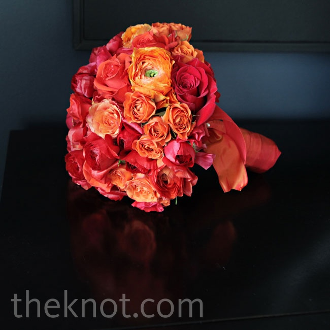 Courtney and her bridesmaids held roses and ranunculus in shades of red and orange.