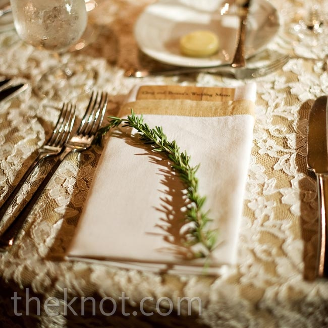 Fresh rosemary sprigs topped ivory napkins and lace linens at the reception.
