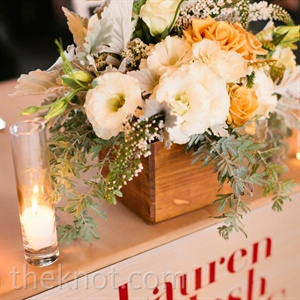 Lauren and Josh's sweetheart table was labeled with a modern sign and topped with a lush centerpiece.