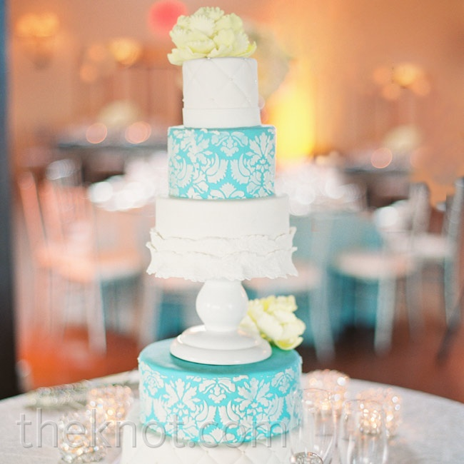 The cake's five tiers had a mix of fondant designs: white quilting, blue-and-white damask and white ruffles.