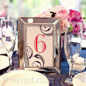 Mirrored frames held table numbers of the same design motif as on the menu cards.