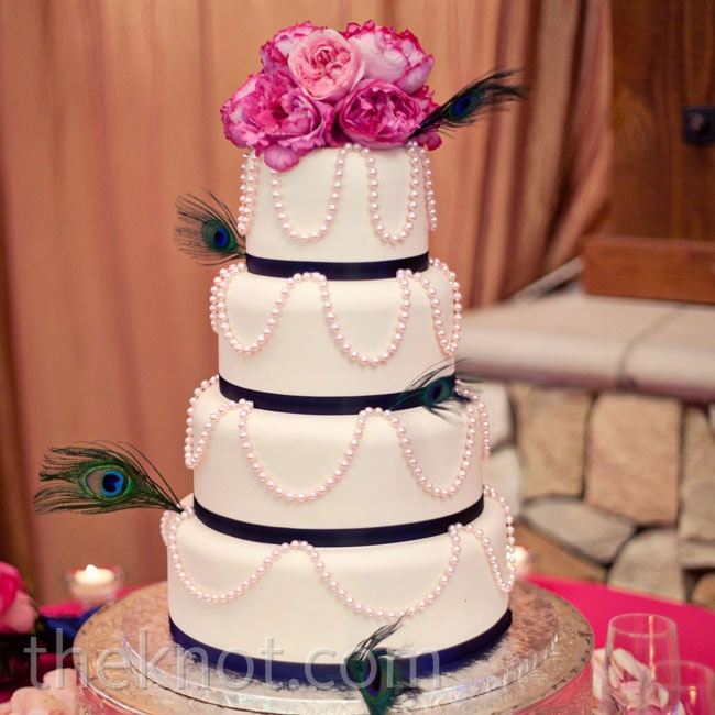The four-tiered white-fondant cake was draped with pearls, wrapped with navy ribbon and finished with fresh flowers and peacock feathers.