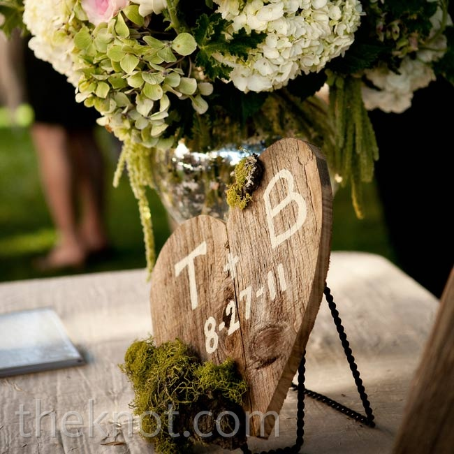 A large bouquet of Polo roses and hydrangeas, along with a distressed wooden heart, decorated the guest book table.