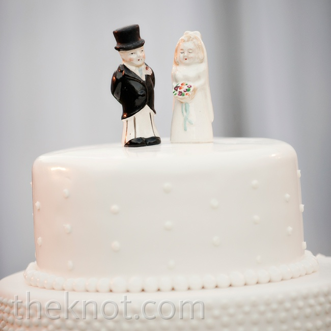 An antique bride and groom cake topper added a sweet touch to the simple three-tiered cake.