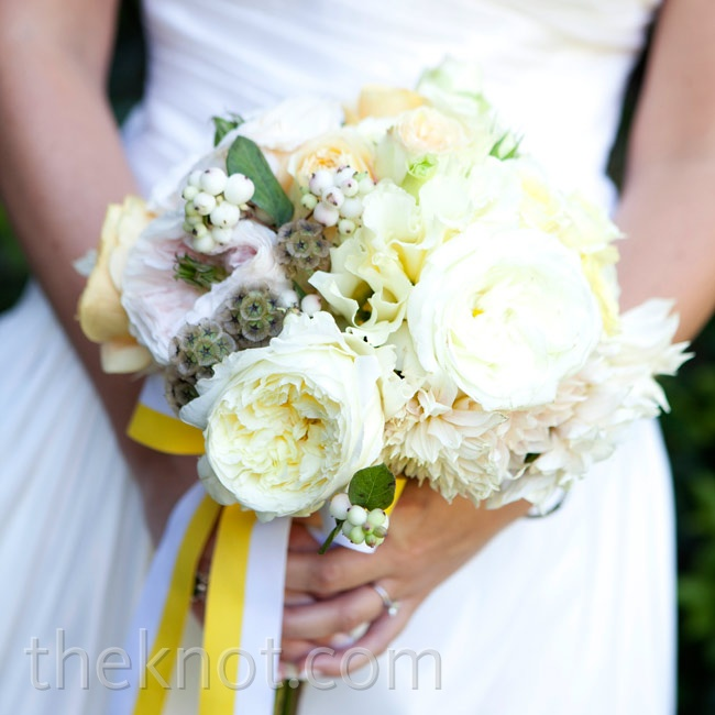 Laura carried a textured bunch of white flowers with berries and scabiosa pods -- all wrapped in yellow and white stripped ribbon.