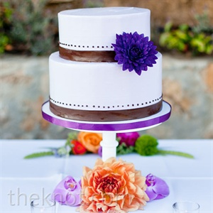 The two-tiered wedding cake was purple with chocolate fondant ribbon around each tier.